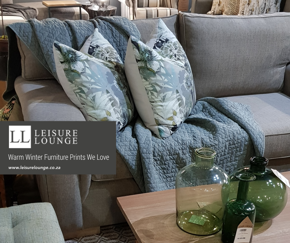 Grey couch with floral print pillows and a duck egg blue throw